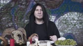 smrt : Suspicious man in the black clothes with the hood on the head sitting at the small table in front of candles, grapes, and the ram skull, talking looking in camera. The dark witcher celebrating Dostupné videozáznamy