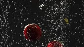 macro shooting : Falling fresh strawberries and cherries splashing into sparkling water on black background. Close-up. Stock Footage