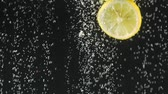 carbonated : Fresh lemon slices falling into the water on black background. Citrus in water with bubbles. Organic food. Slow motion. Stock Footage