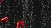 macro shooting : Strawberry halves falling into the water with bubbles on black background. Fresh berries in the water. Organic berry, fruit, healthy food. Slow motion.