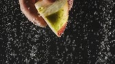macro shooting : Male hand holding apple slice under the water on black background. Fresh fruit in the water with bubbles. Organic food, healthy lifestyle, diet. Summertime concept Stock Footage