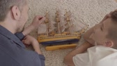 родитель : Portrait adorable father and his son lying at home on the floor on the fluffy carpet playing with ship model close-up. Family spending time together. Back view