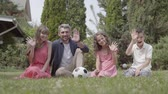 родитель : Happy family sitting on the grass in the garden together. Mother, father, son, and daughter looking in the camera smiling and waving hands. Summertime leisure, carefree childhood Стоковые видеозаписи
