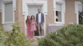 родитель : Cute family standing on the porch together. Mother and father kissing goodbye to little daughter and she leaving house. Summertime leisure