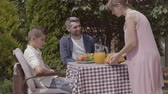 родитель : Woman and the girl bringing pastry. Dad, mom and their two kids sitting at a table, eating lunch in the garden enjoying a sunny day. Summertime, happy family Стоковые видеозаписи
