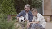 родитель : Father and his son sitting on the porch holding a deflated soccer ball in hands. The man and the boy talking about football. Family spending time together. Summertime leisure, active lifestyle