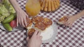 rohlíky : Freshly baked cakes lying on the table near vegetables and juice jar. Hands of mother, father, and children taking pieces of fresh pastry at the same time. Breakfast of happy friendly family