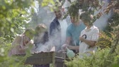 husband : Happy friendly family making bbq in the garden close-up. Summertime leisure. People cooking meat on the grill outdoors