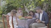 chitarra : Father plays the guitar for his family at a dinner table sitting in the backyard. Friendly family relationships.