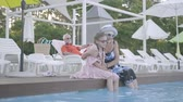 vnouče : Little funny girl with pigtails and mature woman sitting on the edge of the pool with their feet in the water while senior man lying on sunbed in the background. Happy friendly family. Rest in hotel Dostupné videozáznamy