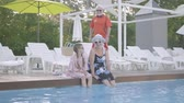 amante : Little cute girl with pigtails and mature woman sitting on the edge of the pool with their feet in the water. Grandfather joing them. Happy friendly family. Rest in hotel Stock Footage
