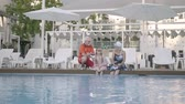 aktive senioren : Happy mature couple with little granddaughter on the edge of the luxury pool. Grandmother, grandfather and grandchild converse. Happy friendly family. Rest in hotel. Recreation and leisure outdoors Stock Footage