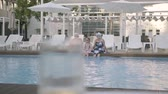 piscina : Fun happy mature couple with little granddaughter sitting on the edge of the luxury pool. Grandmother, grandfather and grandchild converse. Happy friendly family. Rest in hotel. Recreation and leisure outdoors