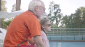 husband : Side view of mature man, woman and little girl sitting on the edge of the pool splashing water with hands. Grandmother, grandfather, and grandchild having fun. Happy friendly family. Rest in hotel