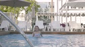 atlama : Little cute girl swims in a beautiful pool at an expensive resort. Recreation and leisure outdoors.