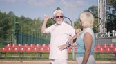 husband : Mature couple in sunglasses and tennis rackets standing on a tennis court in the sun. Recreation and leisure outdoors.
