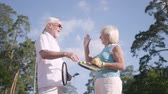 husband : Positive smiling mature couple after playing tennis on the tennis court shaking hands and giving high five. Active leisure outdoors. Senior man and woman having fun together