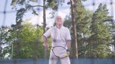 one person only : Joyful happy smiling mature man playing tennis on the tennis court. The old man throws the ball with the racket. Active leisure outdoors.