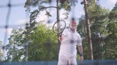 aktive senioren : Positive smiling mature man playing tennis on the tennis court. The old man throws the ball with the racket. Active leisure outdoors. Stock Footage