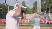 mais velho : The upset mature couple lost the tournament on the tennis court. Senior man and woman holding the head with hands holding rackets. Active leisure outdoors. Concept of defeat Stock Footage