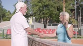 gratitude : Adult woman shakes hands with handsome mature man rival standing on a tennis court in the rays of the summer sun. Recreation and leisure outdoors.