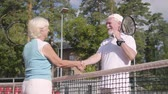 husband : Smiling mature couple shaking hands after playing tennis on the tennis court. Active leisure outdoors. Senior man and woman having fun together Stock Footage