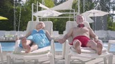 amante : Elderly positive couple lying on sunbeds near the pool holding hands and smiling. Happy loving family. Rest in hotel. Front view Stock Footage
