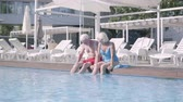 şezlong : Happy mature couple sitting on the edge of the pool with their feet in the water. Cute senior man and woman relaxing in the hotel complex. Happy friendly family. Rest in hotel