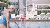 şezlong : Attractive senior woman walking into the pool while her husband sitting in the background. Mature couple relaxing at the pool in the hotel complex together. Happy loving family. Rest in hotel Stok Video