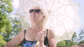 one person only : Portrait of positive smiling mature woman in sunglasses standing in the park under the white parasol looking around and in the camera. Leisure outdoors in hot sunny day