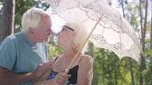 one person only : Portrait of positive smiling mature woman in sunglasses standing outdoors under the white parasol. Senior man meeting his wife in the park, couple kissing. Leisure outdoors in hot sunny day Stock Footage
