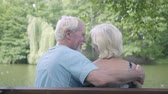 husband : Back view of a happy mature couple sitting on the bench near the river, admiring nature. The man hugging his wife, people kissing. Senior man and woman relaxing together. Leisure outdoors