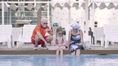 husband : Happy mature couple and their little granddaughter sitting on the edge of the pool. Grandmother, grandfather, and grandchild resting together. Happy friendly family. Front view