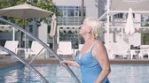 amante : Happy mature couple relaxing at the pool in the hotel complex together. Attractive senior woman sunbathing and waving hand to her husband. Happy friendly family. Rest in hotel