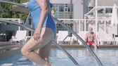 amante : Happy mature couple relaxing at the pool in the hotel complex together. Attractive senior woman sunbathing, comes out of the pool and waving hand to her husband. Happy friendly family. Rest in hotel Stock Footage