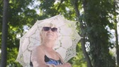 one person only : Portrait of positive smiling mature woman in sunglasses standing in the park under the white umbrella looking around. Leisure outdoors in hot sunny day