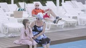 unoka : Grandmother hugs her granddaughter sitting by the pool and look at the camera. Grandfather is resting lying on a sunbed in the background.