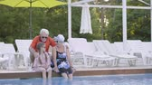 napágy : Little cute girl with pigtails and mature woman sitting on the edge of the pool with their feet in the water. Grandfather joing them. Happy friendly family. Rest in hotel Stock mozgókép