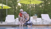 unoka : Portrait mature couple hugging little granddaughter on the edge of the pool. Grandmother, grandfather and grandchild waving hands. Happy friendly family. Rest in hotel. Recreation and leisure outdoors Stock mozgókép