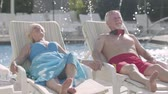 şezlong : Elderly positive couple lying on sunbeds near the pool holding hands and smiling. Happy loving family. Rest in hotel. Front view Stok Video