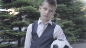 жилет : Portrait cute well-dressed boy standing on the street holding the soccer ball and purse. Serious young man simultaneously acting like child and adult. Стоковые видеозаписи