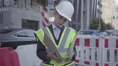 como : Portrait little boy wearing safety equipment and constructor helmet reading building plan, controlling work on a busy road on the background of road signs in a big city. Child as adult.