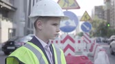 como : Cute little successful boy wearing business suit and safety equipment and constructor helmet standing on a busy road in a big city. Engineer, architect, builder doing his work. Child as adult