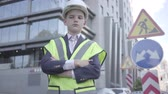 supervise : Portrait cute little successful boy wearing business suit and safety equipment and constructor helmet standing on a busy road in a big city. Engineer, architect, builder doing his work. Child as adult Stock Footage