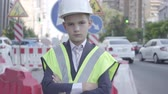 como : Portrait cute little confidient boy wearing business suit and safety equipment and constructor helmet standing on a busy road in a big city. Engineer, architect, builder doing his work. Child as adult