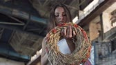 orelhas : The young girl chooses between a military cap and a wreath of wheat in abandoned building. Attractive woman takes a wreath and puts it on her head, smiling. Warrior woman in a deserted factory. Stock Footage