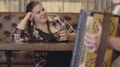 compositor : Unrecognizable man playing the accordion while attractive plump woman drinking beer and sending him air kiss. Concept of russian traditional music. Folk concept