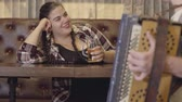 accordionist : Unrecognizable man playing the accordion while attractive plump woman drinking beer and sending him air kiss. Concept of russian traditional music. Folk concept