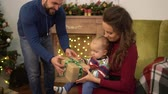 first child : Mother, father and little baby sitting near decorated christmas tree. Dad present box to the child sitting on mother laps. Happy family celebrating Christmas together.