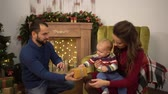 сочельник : Happy family celebrating Christmas together. Mother, father and little baby sitting in the room with christmas decoration. The man gives small present box to the child sitting on mother laps.
